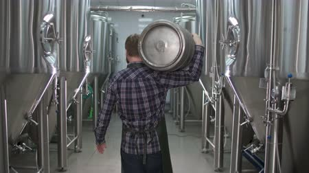 A working male brewer carries a keg filled with beer as he passes beer tanks. back view