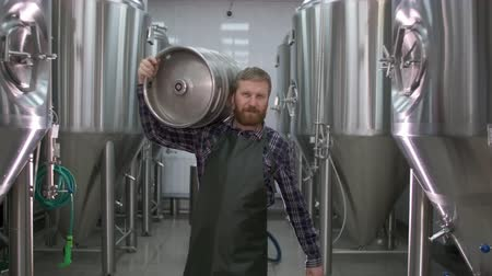 Worker Male brewer carries a keg filled with beer passing beer tanks