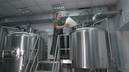 beczka : Worker Male brewer pours crushed malt into a beer tank for the production of craft beer.