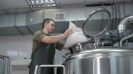 A working male brewer pours crushed malt into a beer tank to produce craft beer. Close-up