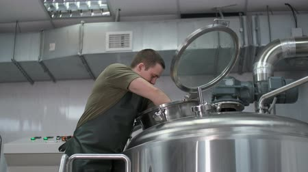 Worker male brewer stirs a mixture for brewing beer in a beer tank
