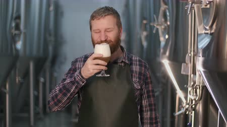 Portrait. Cheerful male brewer tastes freshly brewed beer to taste leaving foam on his mustache while standing in a beer factory