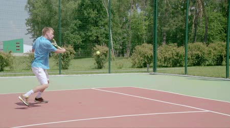 tennis player : Tennis player uses backhand slice on the half court. Slow motion