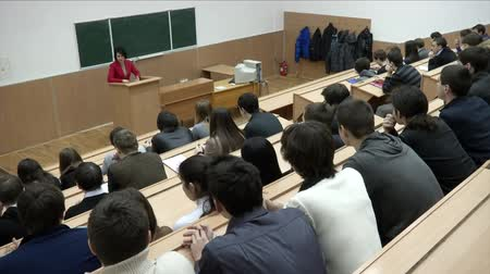 лекция : Students listening to their teacher at the lecture in university. Students sitting inside a lecture hall