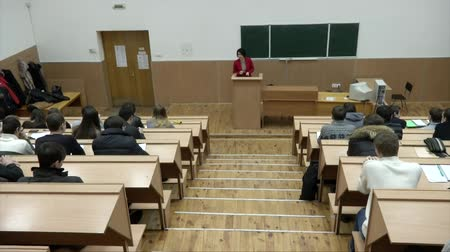 wykład : Students listening to their teacher at the lecture in university. Students sitting inside a lecture hall