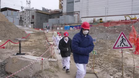 sarcophagus : Workers near protective screen in front of Chernobyl nuclear power plant. Construction of new safe shelter over reactor in the Chernobyl power plant