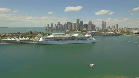 Майами : Aerial, 4K. Hydroplane moving on the Miami harbor near Cruise Ship. USA Port passenger terminal and cruise liner in harbor