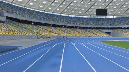 forma : Aerial filming inside of a huge modern empty stadium. Flying above track lines. Kyiv Olympic stadium, Ukraine