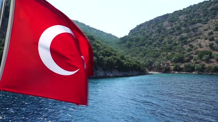 turk : Slow motion. Turkish flag waving on the wind. Sea and mountains on background.