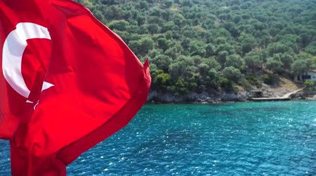 turk : Turkish flag waving on the wind. Sea and mountains on background. Stock Footage