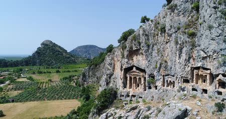 relics : Aerial. Ancient Lycian rock-cut tombs, Fethiye, Turkey. Camera moves down. 4K.