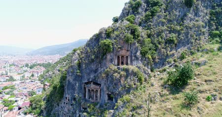 Aerial. Ancient Lycian rock-cut tombs, Fethiye, Turkey. Camera moves up, 4K.