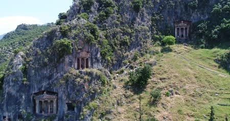 relics : Aerial. Ancient Lycian rock-cut tombs, Fethiye, Turkey. Camera moves up, 4K.