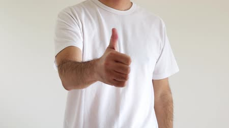 A man who raises his hand and raises his thumbs up