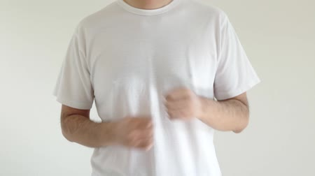 A man wearing a shirt shaking his arms Stock Footage