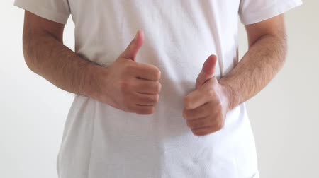 A man wearing a shirt that thumbs up a lot with both hands
