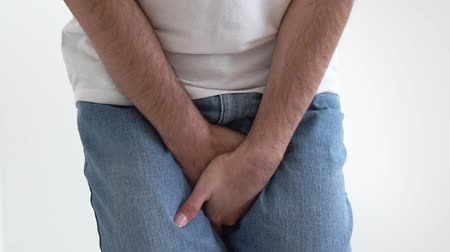 lower part : A man holding his crotch with both hands