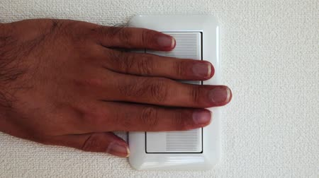 switch : Mans Hand Pushing the Light Switch