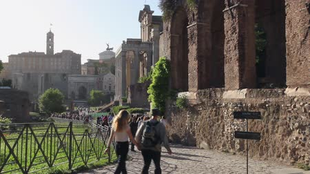 palatine : Rome, Italy - May 7, 2017: Archaeological area of ??Palatine, tourists walk on the ancient sacred street of the Roman Forum. On the right, ancient porch and in the distance the columns of the Temple of Antoninus and Faustina.