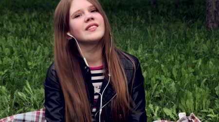 парк : Pretty young girl listening music in headphones in the park