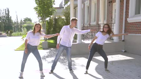 posando : Three girls and boy dressed in similar jeans and shirts dancing in the street