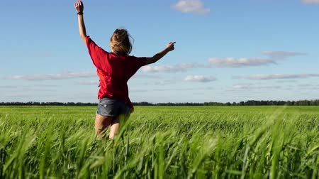 Happy woman enjoying nature beautiful blonde dancing on field. Freedom concept.