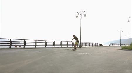 inline skating : Young sporty man learns to roller skate on waterfront