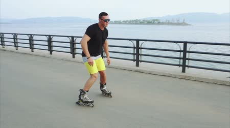jump away : Young sporty man roller skating on summer seafront