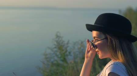 наслаждаться : Young woman in sunglasses sit on the edge of a cliff enjoying the nature