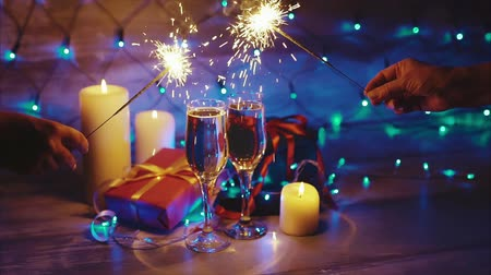 único : Hands with sparklers on the background of Christmas gifts candles and champagne