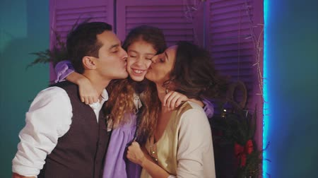 любовь : Concept of happy family parents kissing his daughter christmas background