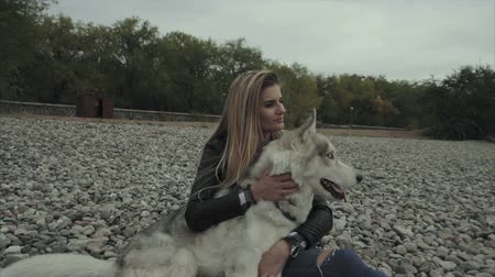 costa : Young pretty woman with siberian husky dog sitting on the river bank
