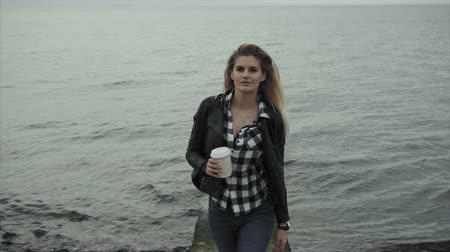 wistful : Cute young blond woman holding a cup of coffee in her hands near the sea