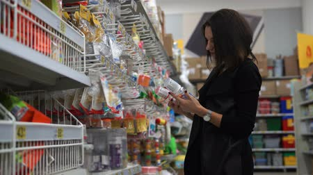 mamilo : Woman mother in a supermarket chooses a small bottle for feeding of the child