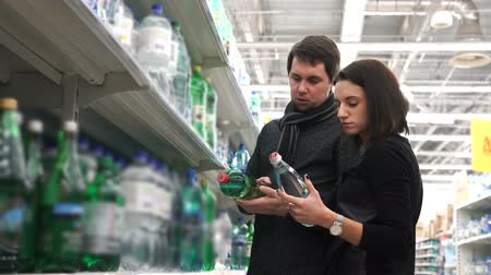 consumismo : Young woman and her husband choose mineral water. Vídeos