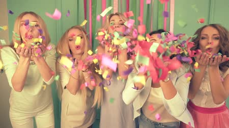 kutluyor : Slow motion shot of five women blowing confetti to the camera at the party. Stok Video