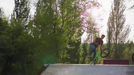 převrátit : Slow motion shot of the young man performing tricks on the BMX bike.