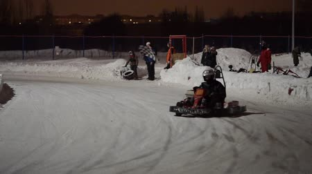 pursue : TOGLIATTI, RUSSIA - JANUARY 6, 2017: Winter amateur competitions karting racing on ice at the night.
