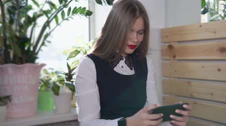 farkında olma : Beautiful business faculty student is watching news on her mobile phone. An adult girl likes to be engaged to be aware of new technologies, on her hand a smart watch for quick viewing of incoming mail Stok Video