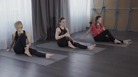 initial : Young women perform an asana in a yoga center called Pashchimotanasana, then they pass into the twist of the spine and return to the initial position Stock Footage