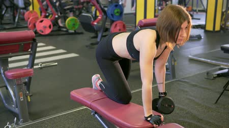 straining : The woman lifts the dumbbells in a half-bent position, leaning on the knee and arm, keeping her back straight and not straining her lower back. This is for the development of muscle mass. Stock Footage