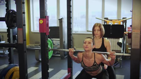 lift ups : An athlete in an elastic suit squats in a sports club. The coach carefully monitors the correctness of the exercise to ensure that the bar with the load does not fall on the client. Stock Footage