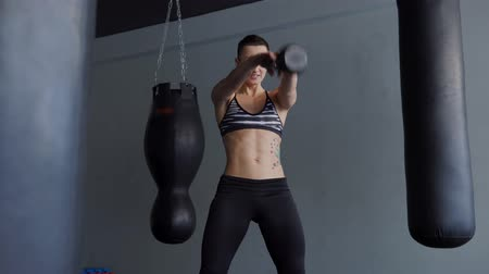 straining : A woman with an athletic body warehouse is engaged with a muscle simulator in the fitness club. Sportswoman throwing a weight from hand to hand, straining the muscles of the triceps and press.