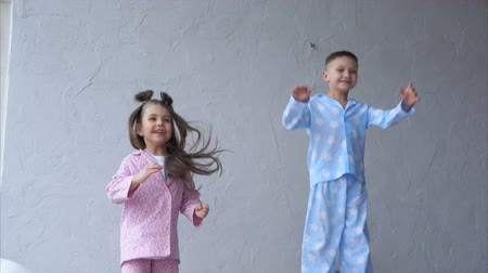 pizsama : A little boy and a pretty girl, dressed in homemade pajamas, jumping high on the bed in the bedroom. Happy and joyful children are actively jumping up, fooling around with each other.