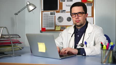 лечит : A doctor at a private clinic who wore a white robe and a stethoscope around his neck sits at the desk, his hands on the laptop keyboard. A man with glasses looks at the camera
