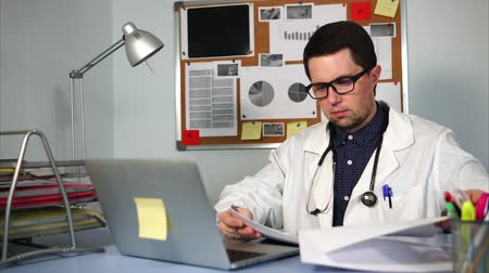лечит : An experienced physician at a private clinic looks at the patients analysis, who has applied for treatment in order to recover. A man in a white coat and a stethoscope on his neck holds the results Стоковые видеозаписи