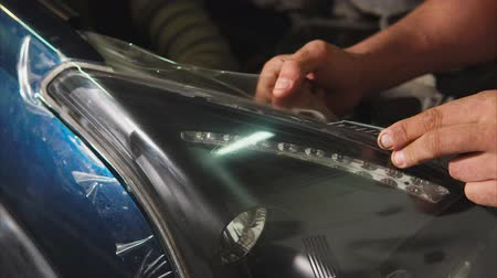 運輸 : Close up shot of the hands of a man who cut the vinyl film on a blue car. In car showrooms it is applied to gently put vinyl on the hood.