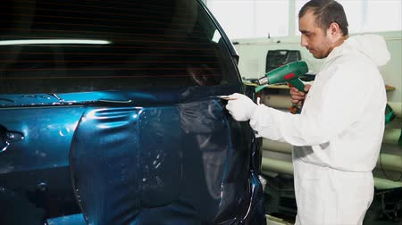 sarıcı : One skilled in the body shop applies a vinyl surface to the vehicle and gradually smoothing squeegee film pastes. Need to remove all air bubbles, which are formed under the film.