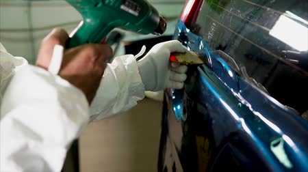 pastas : Close up shot of man applying vinyl film while tuning expensive blue car. Stock Footage