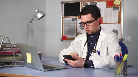 лечит : A young doctor in a white lab coat and a stethoscope on the neck examines X-rays on a mobile phone in the private clinics office. A man heals patients using a laptop and other gadgets